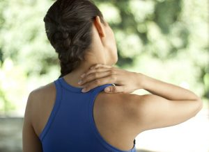 Junge Frau in Sportbekleidung hält sich mit der Hand den Nacken.